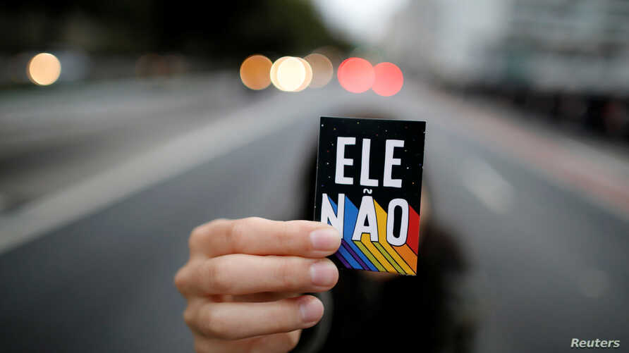 """A demonstrator shows a sticker that reads """"Not him"""" during a protest against Brazilian presidential candidate Jair Bolsonaro at Paulista Avenue in Sao Paulo, Brazil, Oct. 6, 2018."""