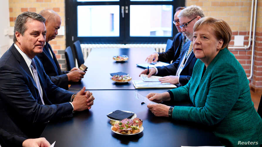World Trade Organization (WTO) chief Roberto Azevedo President (L) and German Chancellor Angela Merkel hold talks on the sidelines of a conference organized by the Federation of German Industries (BDI) IN Berlin, Germany, Sept. 25, 2018.