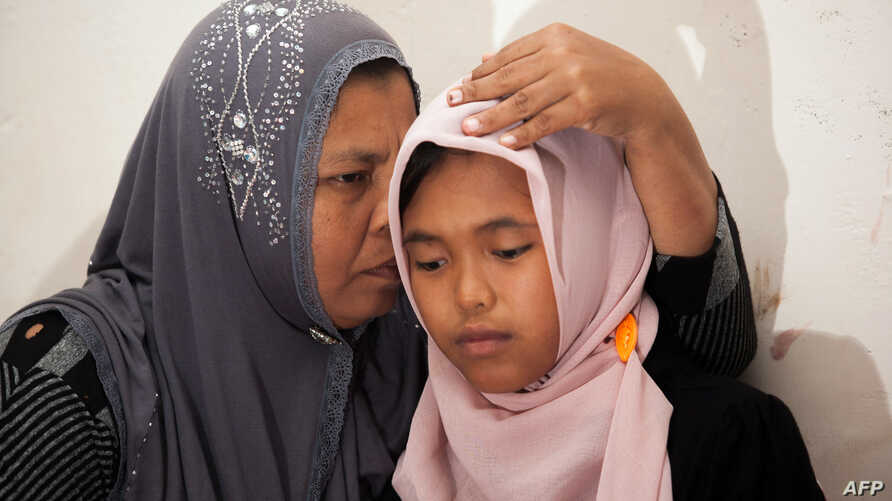 Indonesian mother Jamaliah (L) hugs her daughter Raudhatul Jannah (R) after they were reunited in Meulaboh, Aceh province, August 7, 2014.