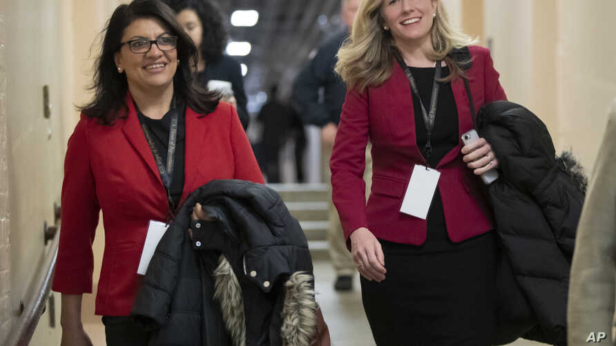 FILE - Rep.-elect Rashida Tlaib, D-Mich., left, and Rep.-elect Abigail Spanberger, D-Va., head to a Democratic Caucus meeting in the basement of the Capitol