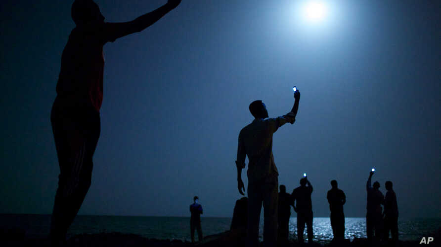 In this photo provided on Feb. 14, 2014 by World Press Photo, the World Press Photo of the Year 2013 by John Stanmeyer, USA, VII for National Geographic, shows African migrants on the shore of Djibouti city at night, raising their phones in an attemp