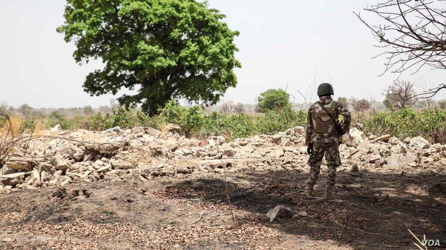A Nigerian soldier stands amid the rubble of the Government Secondary School in Chibok, Nigeria on March 25, 2016. (Photo: Chris Stein for VOA)