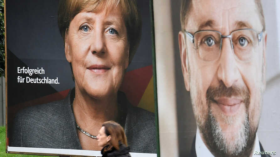 Election posters of German Chancellor Angela Merkel of the Christian Democratic Party CDU and Social Democratic Party SPD leader and top candidate Martin Schulz are seen in Hamburg, Germany, Sept. 24, 2017.