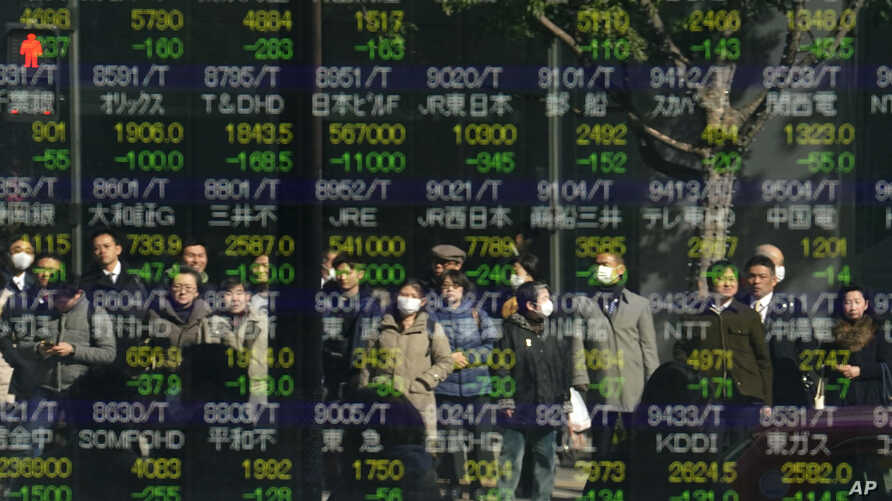 People are reflected on an electronic stock indicator of a securities firm in Tokyo, Tuesday, Feb. 6, 2018.
