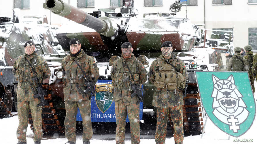 German soldiers pose in front of a Leopard 2 tank during German Minister of Defense Ursula von der Leyen's visit to German troops deployed as part of NATO enhanced Forward Presence (battle group in Rukla military base, Lithuania, Feb. 4, 2019.