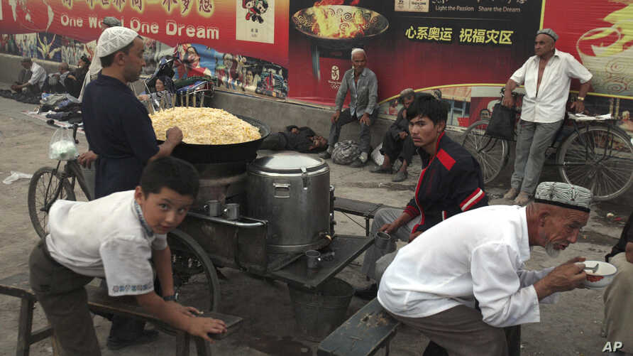 FILE - Uighurs rest near a food stall and Beijing Olympic Games billboards in Kashgar in China's western Xinjiang province, Aug. 30, 2016.