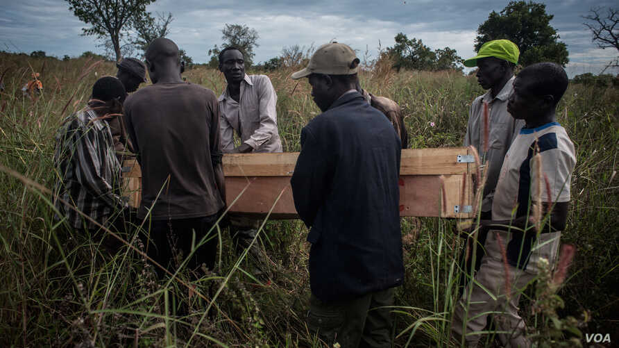 Pallbearers at the border of South Sudan and Uganda carry the casket containing the remains of Duku Evans, a civilian killed November 3 amid fighting between government troops and rebels in Logo displaced persons camp in Kajo Keji, South Sudan, Nov.