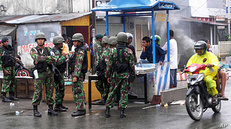 Soldiers stand guard along a road after Sunday's riots in Ambon September 12, 2011. Several people were killed and dozens injured when riots broke out on Sunday after rumors spread online that a motor taxi driver was tortured to death by a group of r