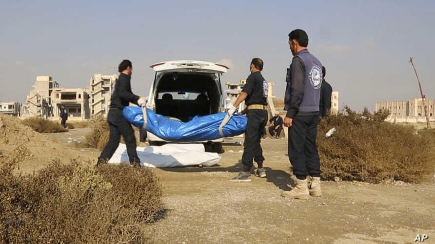 FILE - A frame grab from video provided Nov. 22, 2018, shows Syrian workers carrying human remains at the site of a mass grave believed to contain the bodies of civilians and Islamic State militants, in Raqqa, Syria.