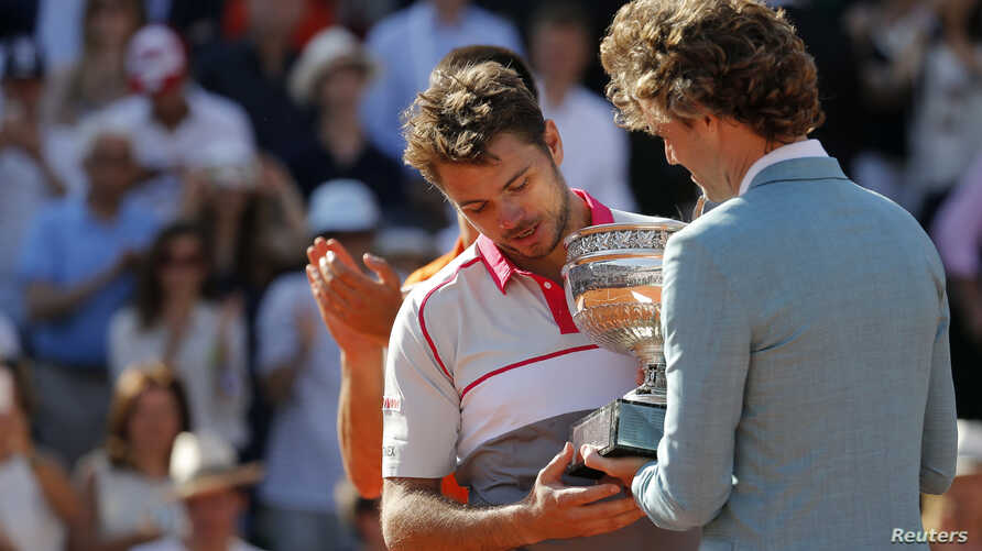 Former Brazilian tennis player Gustavo Kuerten (R) gives the trophy to Stan Wawrinka of Switzerland during the ceremony after he won the men's singles final match against Novak Djokovic of Serbia at the French Open tennis tournament at the Roland Gar