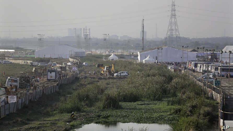 An earthmover is used to level the surface for traffic movement at the site of World Culture Festival organised by Indian guru Sri Sri Ravi Shankar's Art Of Living foundation on the flood plain of Yamuna River in New Delhi, India, Wednesday, March 9,