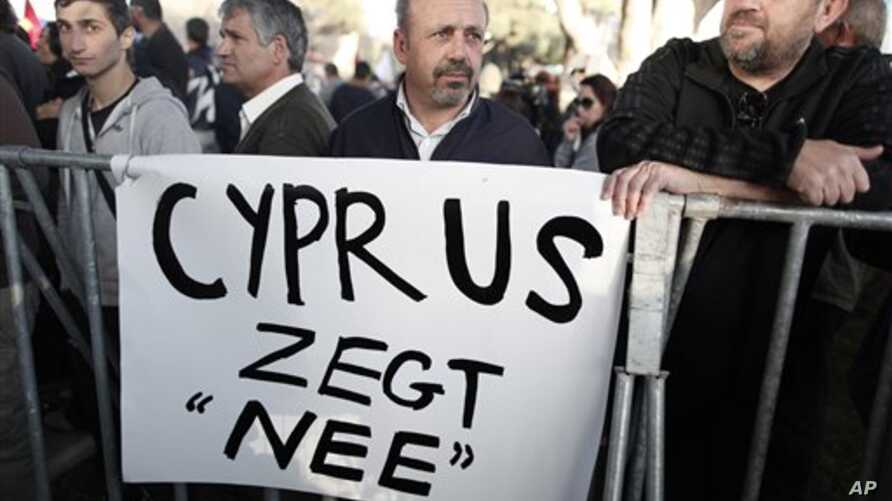 Protesters stand during parliamentary vote on a bank tax plan March 19, 2013 in Nicosia