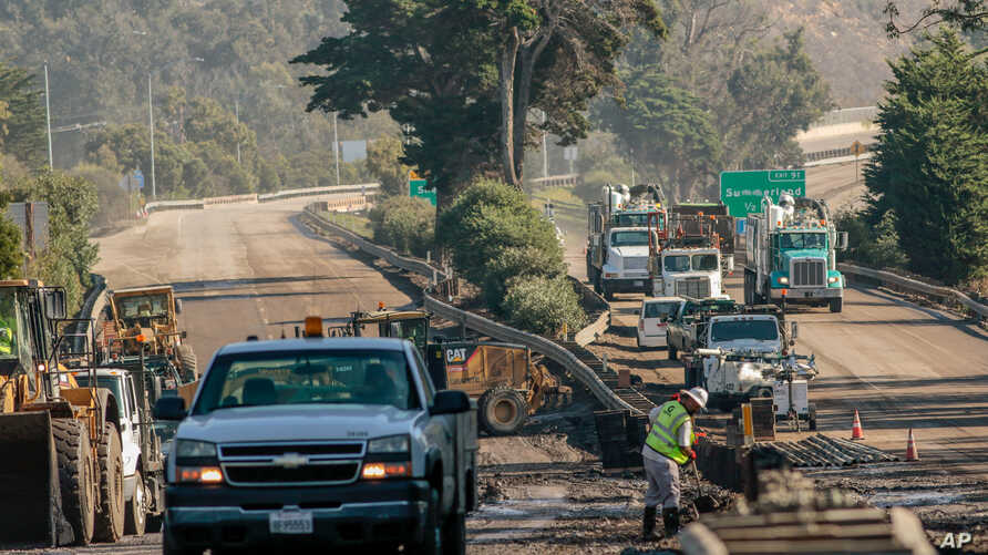 Workers on the 101 Highway clear mud and debris from the roadway after a mudslide in Montecito, California, U.S. January 12, 2018.