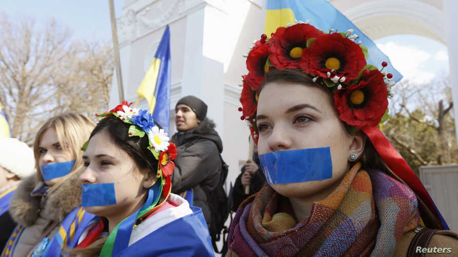 Women with their mouths taped over attend a pro-Ukraine rally in Simferopol, March 13, 2014.