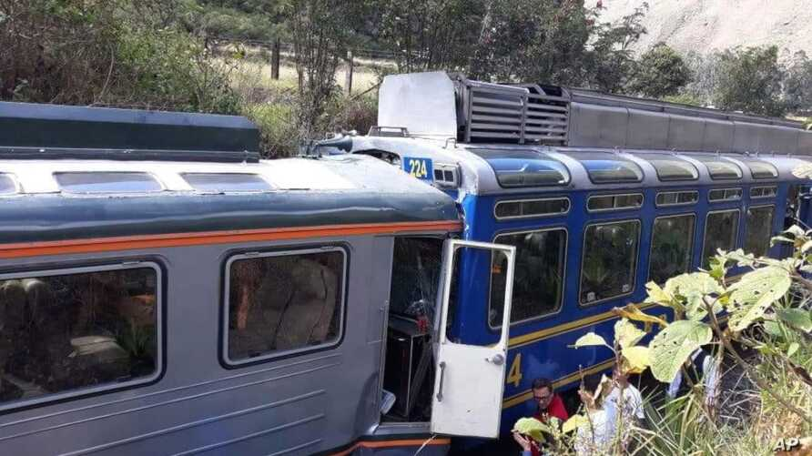In this photo provided by the government news agency Andina, passengers observe two trains after they collided in Cuzco, Peru, July 31, 2018. The two trains collided near the ancient Incan citadel of Machu Picchu, a prized archaeological site in Peru