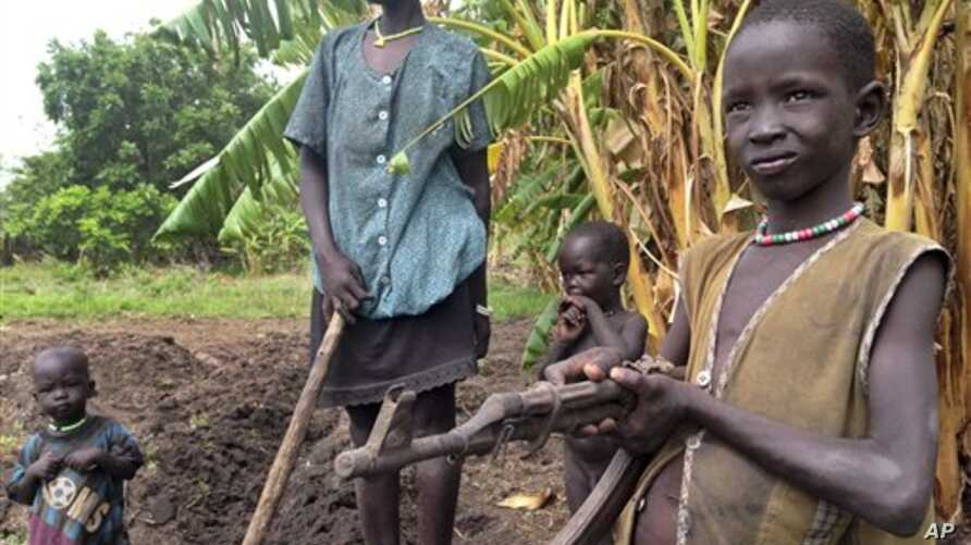 In this photo taken Tuesday, May 6, 2014 and made available Tuesday, May 13, 2014, John Kawai Lam, 8, right, plays with a non-functioning automatic rifle that he found buried in the soil when he and his mother Tabitha Nyanyun Ruach, 38, center, were