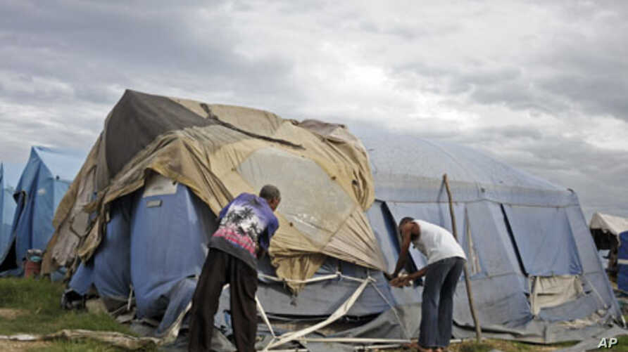 Men try to tie down their tent, which serves as their home, as Tropical Storm Emily idles just south of the slum area of Cite Soleil, Haiti, August 4, 2011