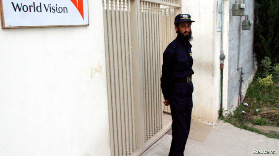 FILE - A security guard stands in front of the World Vision office in Mansehra, north of Islamabad, July 25, 2006.