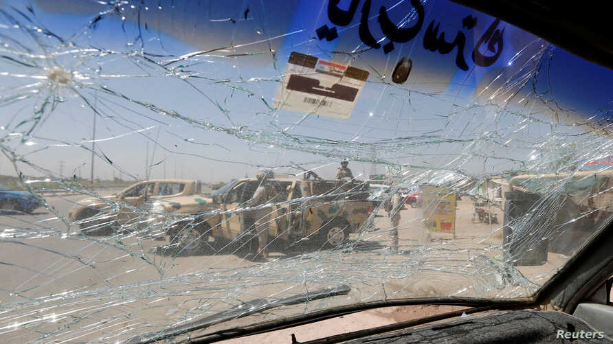 An Iraqi security vehicle is pictured through a shattered windshield of a vehicle damaged at the site of car bomb attack in Rashidiya a district north of Baghdad, Iraq, July 12, 2016.