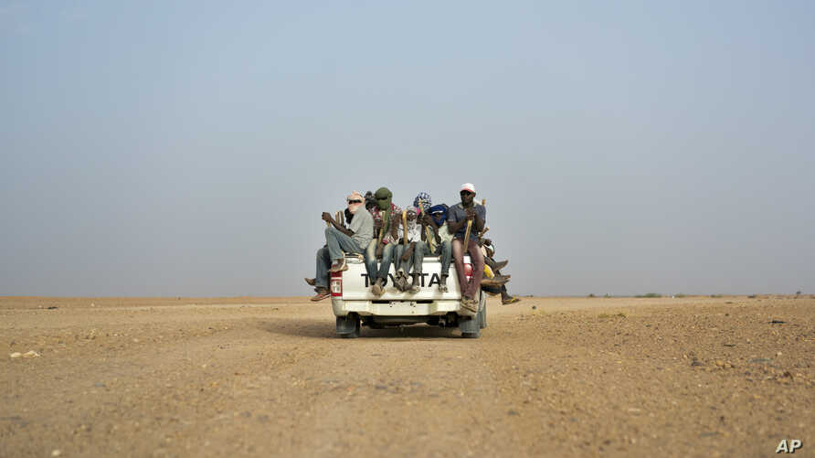 FILE - Nigeriens and third-country migrants head towards Libya from Agadez, Niger, June 4, 2018. Algeria's deadly expulsions of migrants into the Sahara Desert have nearly ground to a halt after widespread condemnation and the abrupt firing of two ...