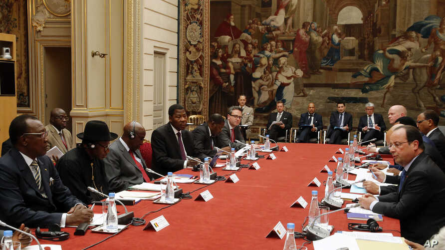"""French President Francois Hollande, right, talks during the round table photo at the """"Paris' Security in Nigeria summit"""", at the Elysee Palace, in Paris, May 17, 2014."""