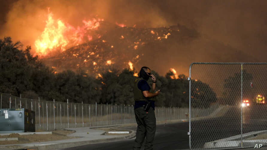 A sheriff's deputy stands guard at a gate near a hillside as the Holy Fire burns in the Cleveland National Forest at Temescal Valley in Corona, Calif., Aug. 9, 2018.