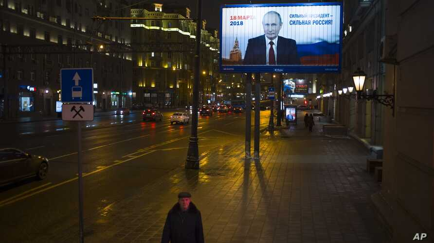 A man walks past a Russian President Vladimir Putin's campaign poster reading 'Strong president - strong Russia' and 'Presidential elections will be held in Russia in March 18' in Moscow, Jan. 15, 2018.