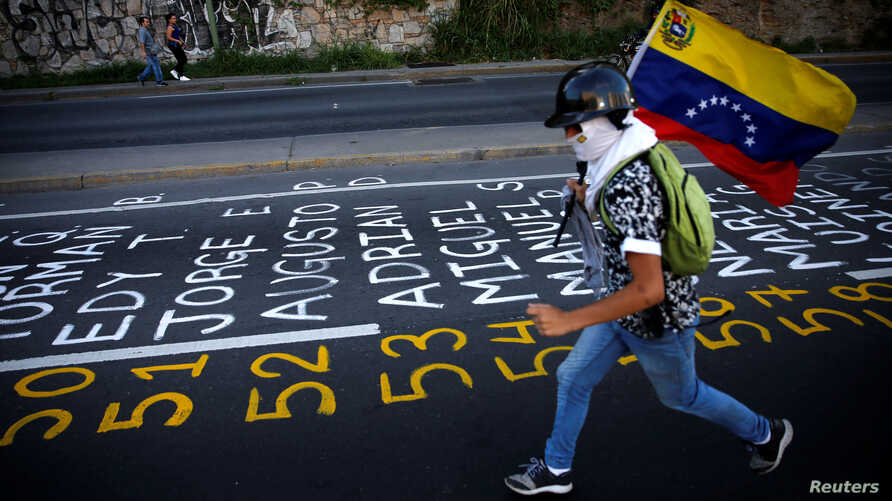 A demonstrator carries a Venezuelan flag as he runs next to a list of the victims of the violence during protests against Venezuela's president Nicolas Maduro government in Caracas, Venezuela, June 12, 2017.