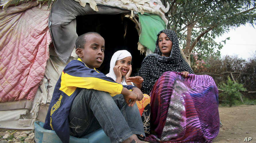 Ubah Mohammed Abdule, 33, right, sits with her son Abdullahi Yusuf Ahmed, 8, left, and daughter Neshad Yusuf Ahmed, 5, center, outside her hut in the Shedder refugee camp in far eastern Ethiopia.