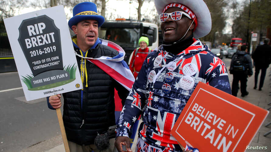A pro-Brexit protester stands with anti-Brexit campaigner Steve Bray outside the Houses of Parliament in London, March 13, 2019.