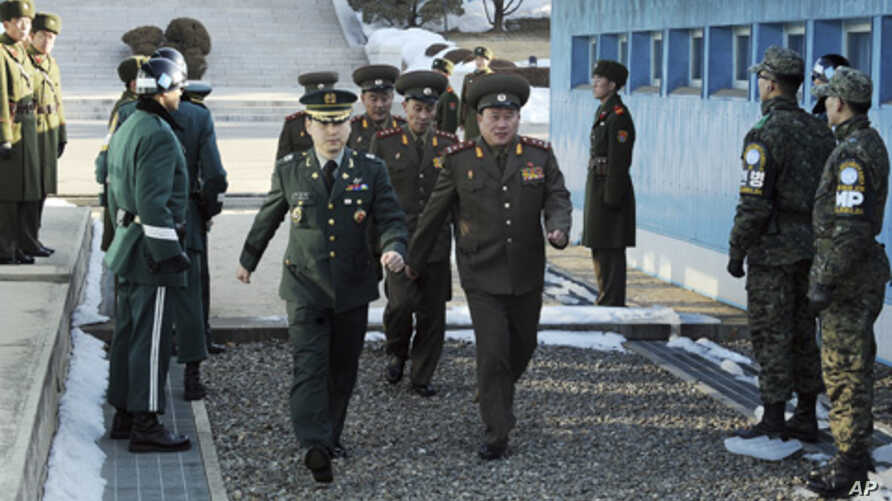North Korean Colonel Ri Son-kwon (front R) and other North Korean delegates cross the border escorted by a South Korean solder (front L) for military talks at the truce village of Panmunjom in Paju, February 9, 2011.