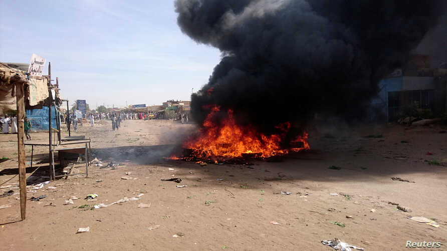 FILE - A bonfire is lit along a street during protests against price increases in Atbara, Nile River state, Sudan, Dec. 20, 2018.