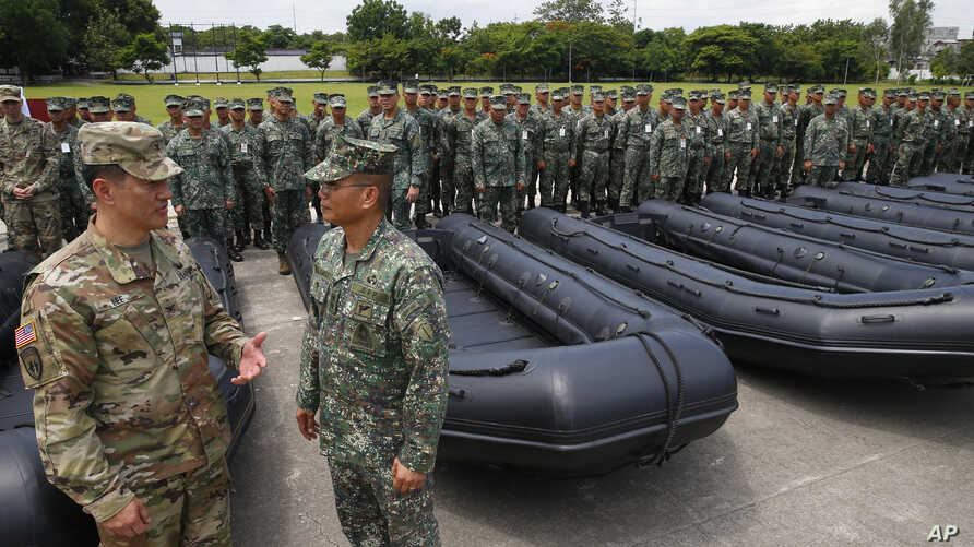 U.S. Army Col. Ernest Lee (left) inspects with Philippine Marine Corps Commandant Maj.Gen. Emmanuel Salamat, military weapons and equipment from the U.S. military to the Philippine marines, June 5, 2017. The new weapons will be used to fight terroris