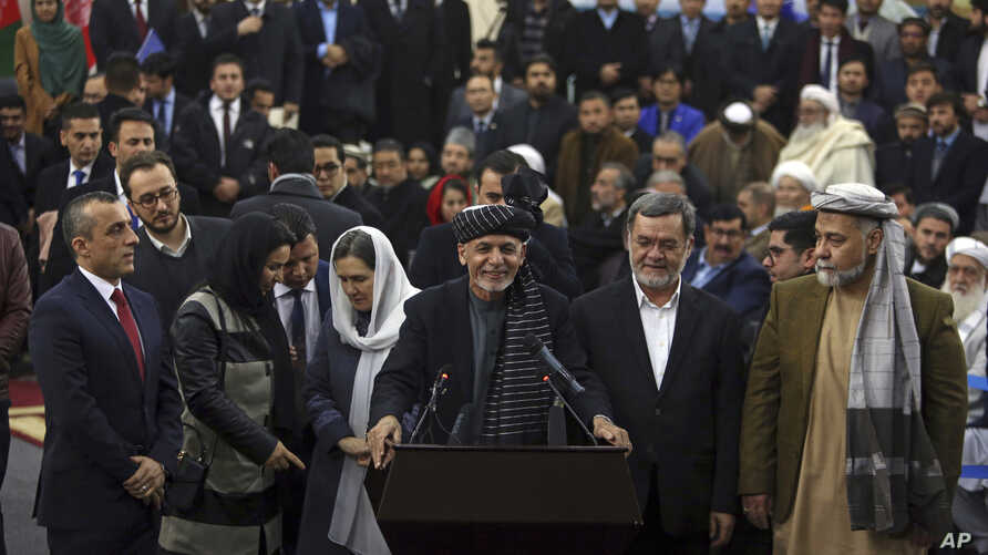 Afghanistan's President Ashraf Ghani, center, speaks to journalists after arriving to register as a candidate for the presidential election at the Independent Elections Commission, in Kabul, Jan. 20, 2019.