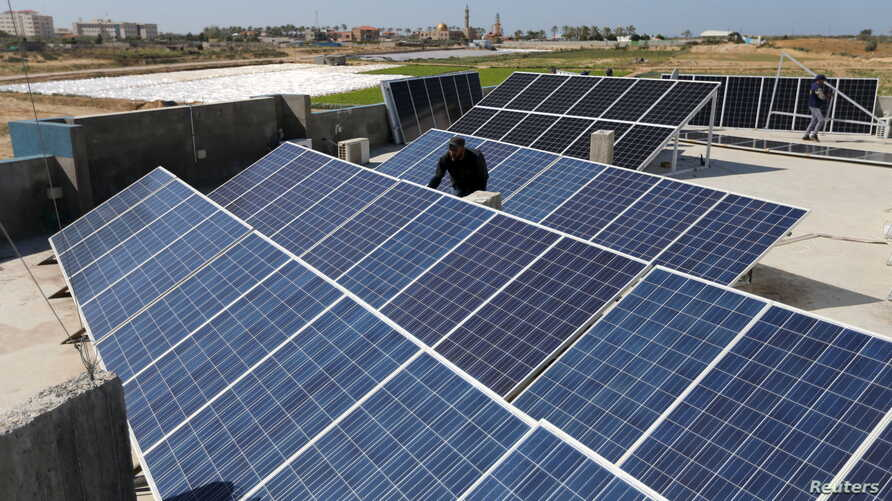 A Palestinian worker installs solar panels atop the roof of a medical center in Gaza City, March 1, 2016.