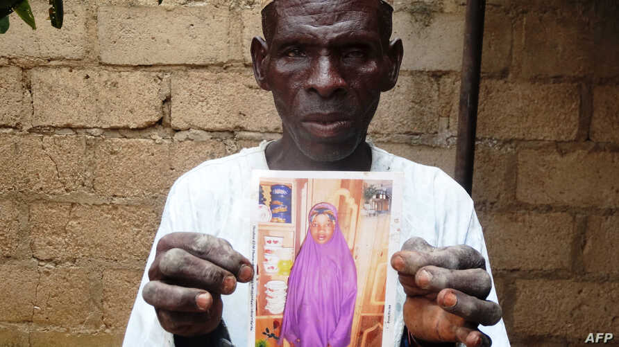 FILE - Sani Garba, 55, holds a picture of his then 14-year-old daughter-in-law Wasila Tasi'u, in Unguwar Yansoro, 63 kilometers north of Kano, Nigeria. Charges were dropped against the girl, now 15, who was accused of killing her 35-year-old husband.