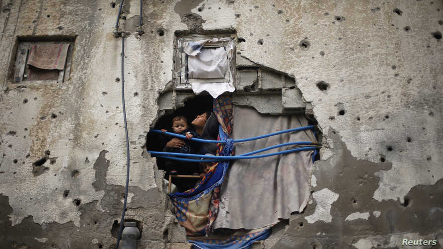 Palestinian children look out through a hole covered with a blanket in their family house, that witnesses said was damaged by Israeli shelling during a 50-day war last summer, in the east of Gaza City January 7, 2015. Heavy rains and near-freezing te