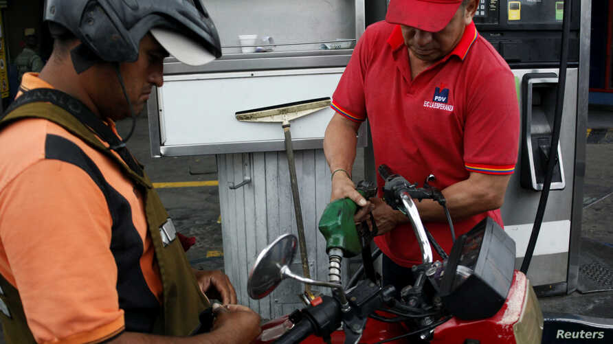 A gas station worker pumps gas into a motorbike at a gas station of the Venezuelan state-owned oil company PDVSA in San Antonio, Venezuela, Sept. 4, 2018.