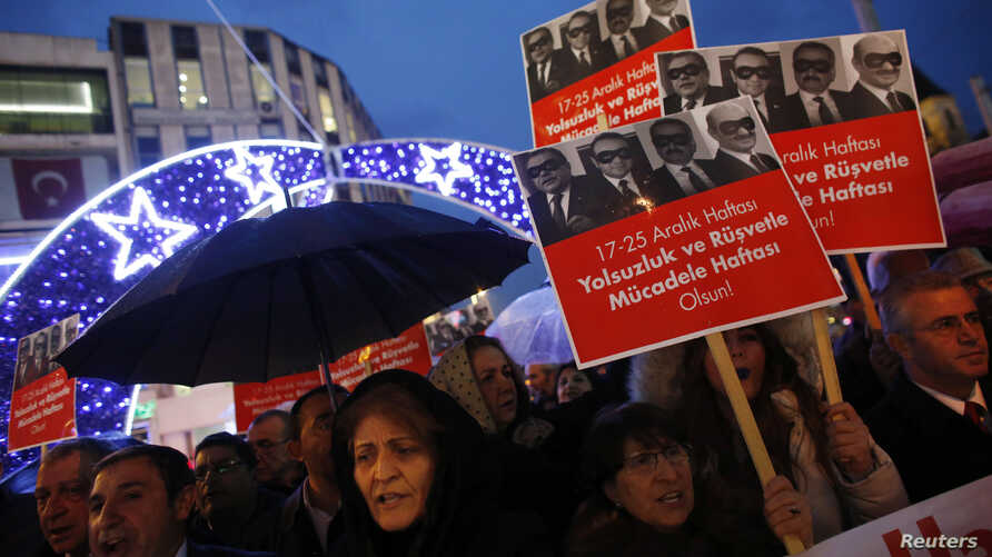 Supporters of main opposition Republican People's Party (CHP) hold placards with pictures of four former ministers while shouting anti-government slogans during a protest in Istanbul, Turkey, Dec. 17, 2014.