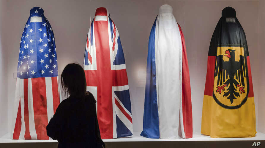 """A visitor walks by an installation by Haitian artist Jean Ulrick Desert, titled The Burqa Project-On The Borders of My Dreams I Encountered My Double's Ghost for an exhibition """"Islam, It's Also Our History"""" at the Espace Vanderborght in Brussels, Sep"""