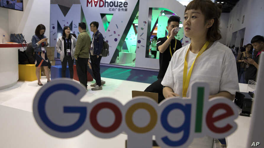 Visitors talk to staff members at a Google stand during the Global Mobile Internet Conference (GMIC) in Beijing, China, April 28, 2017. Google's search engine and email service remains blocked in mainland China but Chinese companies make use of its ...