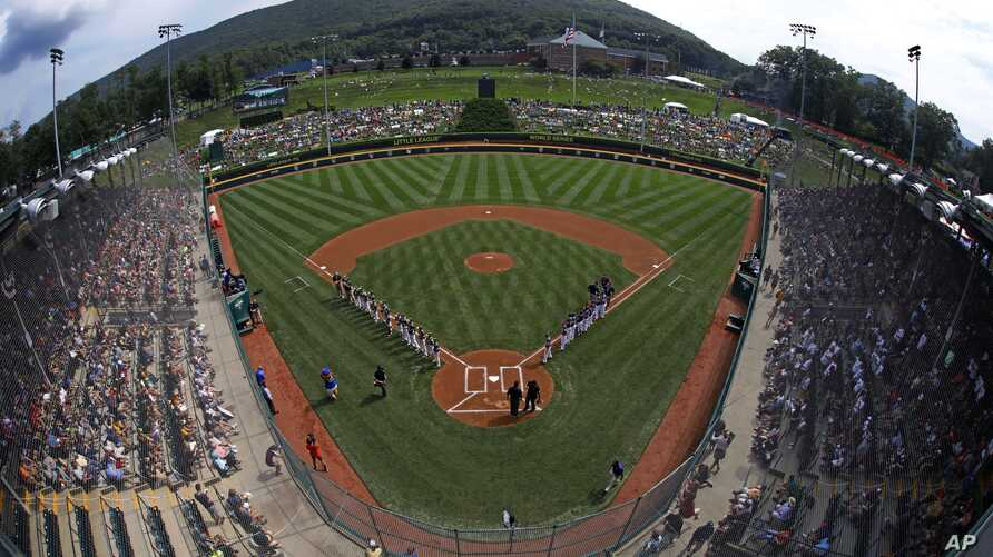 The team from Grandview Little League in Des Moines, Iowa, lines the third base line as the Staten Island, New York, team is introduced in Lamade Stadium before a baseball game in U.S. pool play at the Little League World Series baseball tournament i