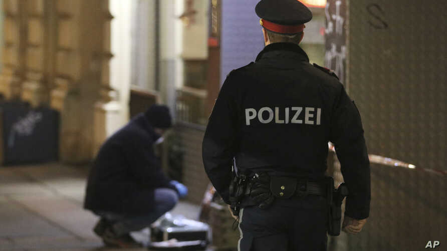 A police officer stands near a forensic expert after three people had been injured in a knife attack on the streets of Vienna, Austria, March 7, 2018.
