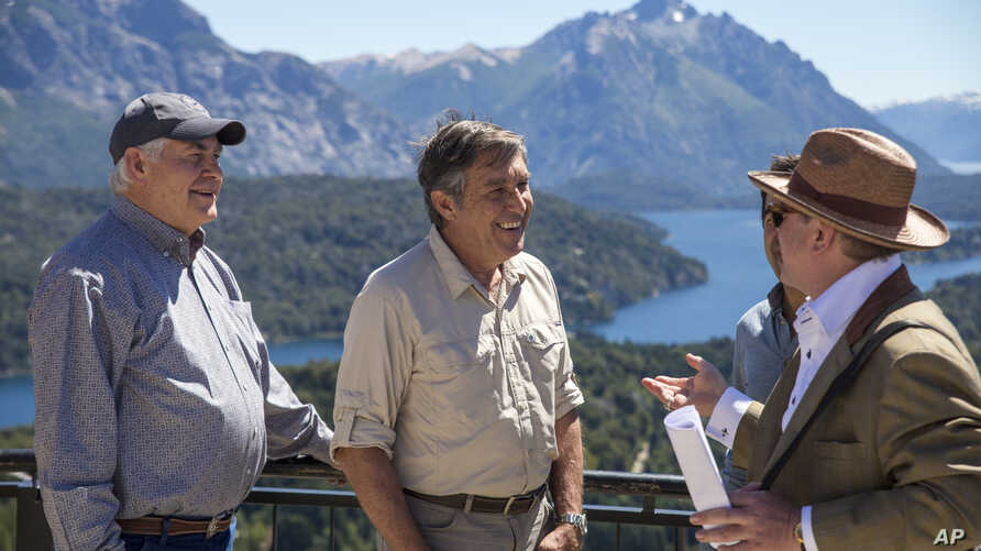 U.S. Secretary of State Rex Tillerson, left, and Eugenio Breard, center, director of Argentina's national parks, stand on a deck overlooking the Nahuel Huapi lake in Bariloche, Argentina,  Feb. 3, 2018. Tillerson spent a day in Argentina's Patagonia