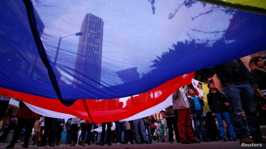 Supporters rallying for the nation's new peace agreement with FARC hold a giant flag during a march in Bogota, Colombia, Nov.15, 2016. The accord is expected to be signed Thursday, Nov. 24, 2016.