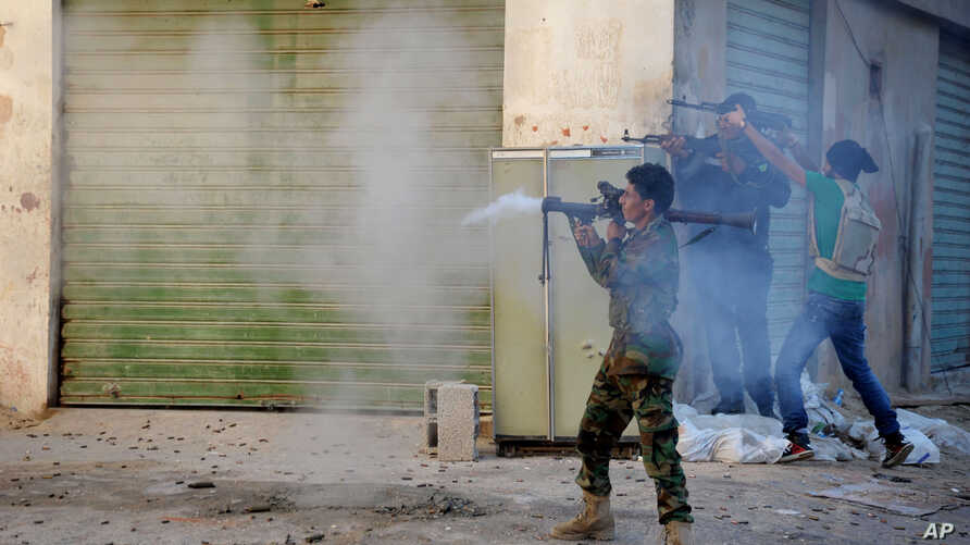 FILE - Libyan military soldiers fire weapons during clashes with Islamic militias in Benghazi, Oct. 29, 2014.