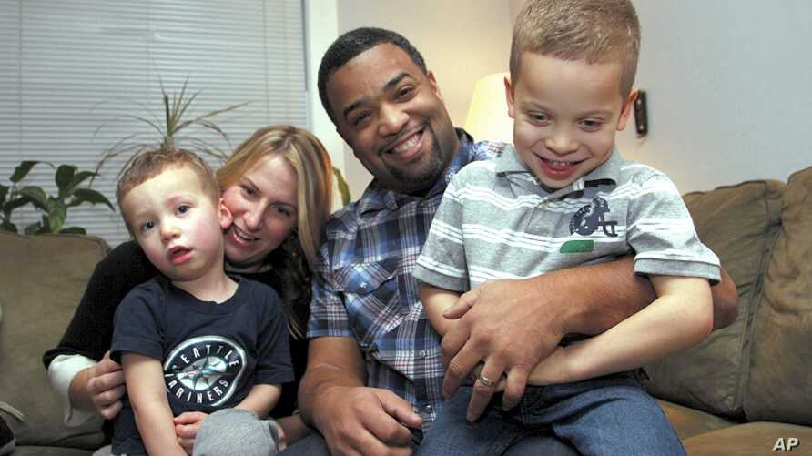 "Damon Brown sits with his wife, Bethany, as they hold their sons Theo, 3, left, and Julian, 5, at their home in Seattle. Damon Brown found a kidney on Facebook after telling his story on a special page the Seattle dad created under the name, ""Damon K"