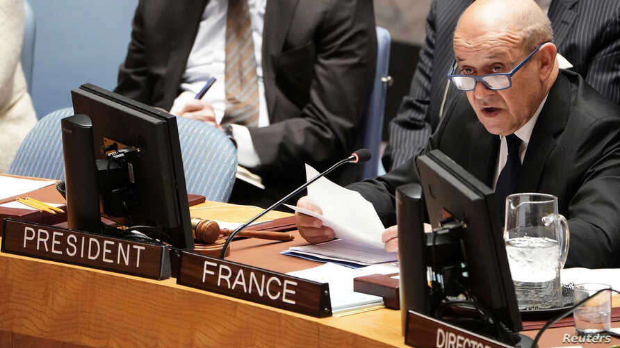 French Foreign Minister Jean-Yves Le Drian speaks with an aide at the United Nations during a meeting about combatting the financing of terrorism in New York, March 28, 2019.
