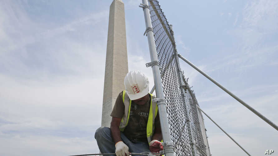 A worker removes fencing which closed the Washington Monument off to the public during renovations, May 9, 2014, in Washington, D.C.