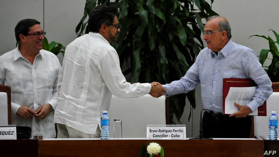 FARC guerrilla commander Ivan Marquez, center, and the head of the Colombian delegation for peace talks, Humberto de la Calle, shake hands after signing a new peace agreement next to Cuban Foreign Affairs Minister Bruno Rodriguez Parrilla in Havana,